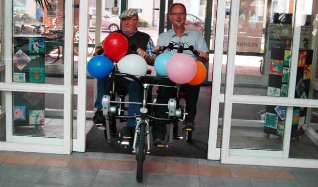 Nadat teamleider Harold Koerntjes (rechts) van Liemerij Meulenvelden de duofiets in ontvangst had genomen, reed hij met bewoner meneer Van Dulmen zaterdagmiddag nog een rondje. (foto: Natasja Scheerder)