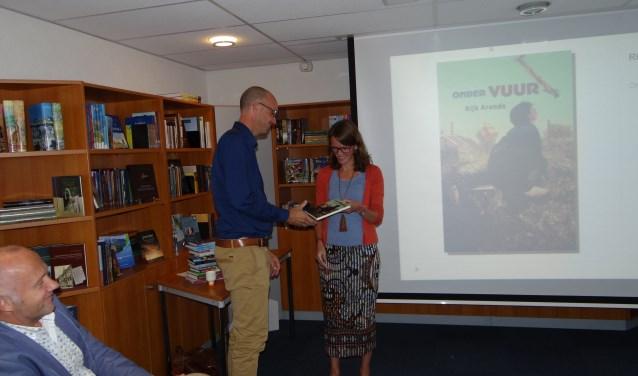 Schrijver Rijk Arends overhandigt het eerste exemplaar van zijn kinderboek 'Onder vuur', dat gaat over de Opheusdense geschiedenis. (Foto: Marco Mauritz)