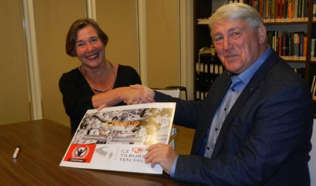 Jolande Grijsbach overhandigt, namens de CZ Tilburg Ten Miles, de cheque aan Bart Franken van het Verbeeten Fonds.