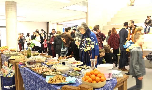 Een overvolle tafel met eten, meegenomen door de aanwezigevluchtelingen. FOTO: Els van Stratum