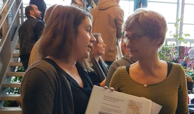 Simone van der Sluijs van DOENJA dienstverlening overhandigt de map aan Wendie de Pater van het Taalcafe.