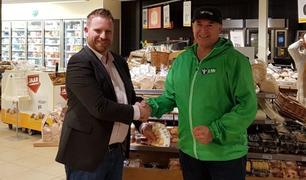 Bedrijfsleider Pieter van der Sluijs van Jumbo Hedel overhandigd het geld aan Peter de Waal van Stichting Tandem Team El Toro