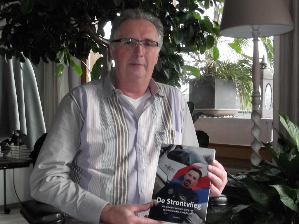Twan Klomp thuis met een exemplaar van 'De Strontvlieg' waarin hij zijn ervaringen als politiepiloot heeft vastgelegd. Foto: Idor van Duppen.