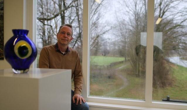 """Joost zit bij het raam van het Kunstgemaal dat uitkijkt op het wandelpad langs de Groote Beek. """"De kunst buiten zal vooral in het gras tussen het gebouw en de wei komen staan. Heel intiem en beschut."""" (foto: Feikje Breimer)"""