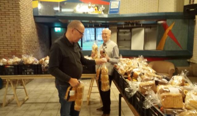 De vrijwilligers vullen de pakketten met het aangeleverde brood