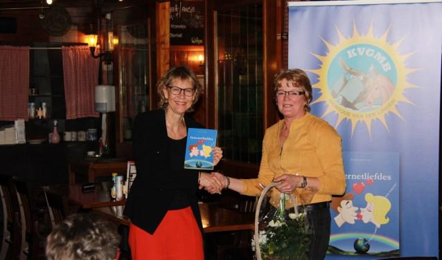 Tijdens de boekpresentatie neemt wethouder Jolanda de Witte het exemplaar in ontvangst uit handen van Monique van der Linden.