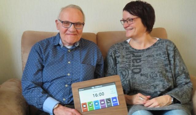 De heer Slijper en zijn dochter Marjon laten De Compaan zien. Hij is uitgevoerd in een lijst van duurzaam hout, zodat hij stevig op tafel staat en doet denken aan een fotolijstje. (FOTO: René Kerkhoven)