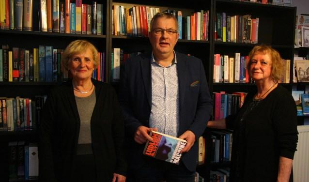 Wethouder Piet de Klein heeft zojuist een boek geleend. Vrijwilligsters Dinie en Ellen hebben de wethouder het boek overhandigd.