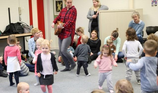 Docent Simone Ruesink speelde leuke liedjes op de gitaar en de aanwezigen dreumesen peuters konden niet stil blijven staan. De kleine voetjes gingen al snel van de vloer. (foto: PR)