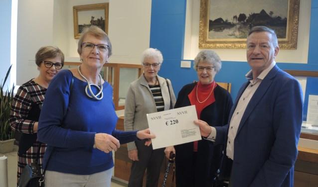 Vertegenwoordigers van NVVH-Vrouwennetwerk doneerden het museum hun Jaarproject. Voorzitter Theo van Hardeveld neemt de cheque in ontvangst. (Foto: Nico van Ginkel)