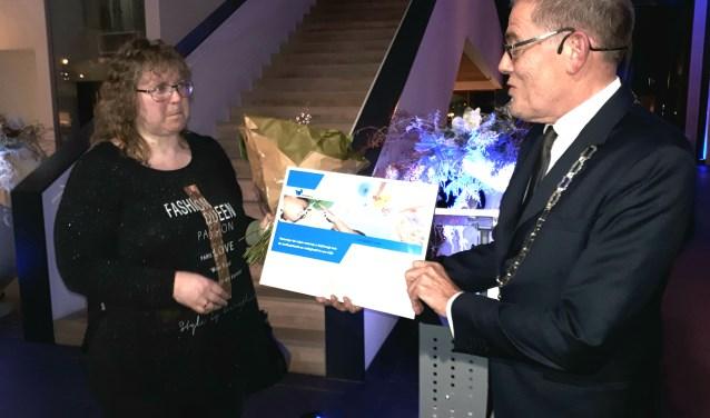 Ria van Londen neemt de Oog voor Veenendaal-prijs in ontvangst uit handen van burgemeester Piet Zoon tijdens de nieuwjaarsreceptie in het gemeentehuis. (Foto:  Jaap Pilon)