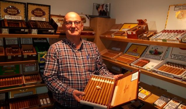 """Victor van Hoof in de vrijgekomen ruimte nu de pinautomaat weg is. """"Hier liggen de beste sigaren uit alle windstreken van de wereld en met een speciaal luchtbevochtigingssysteem houd ik de sigaren in topconditie."""" FOTO: Marcel Bos"""