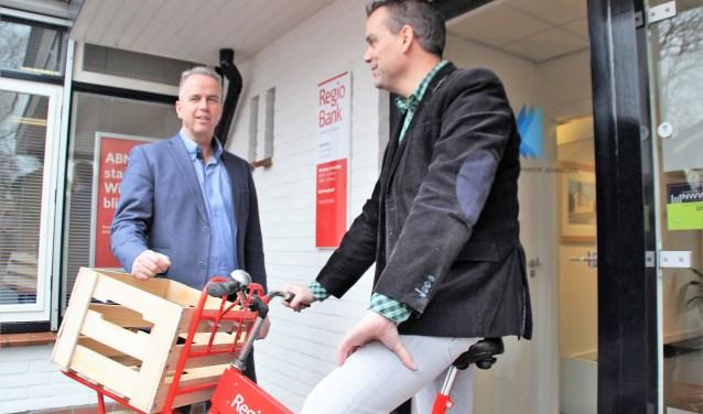 Frank Visser, directeur Leemans Adviseurs, met op de fiets Niek Veldkamp, het gezicht voor bankzaken. Foto Dick Baas