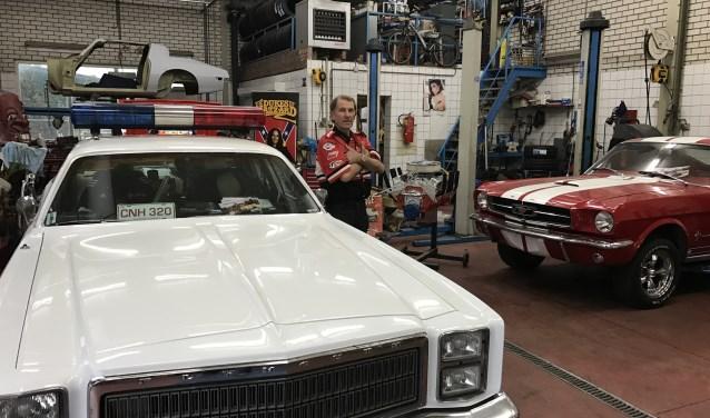 Rob Finders bij enkele klassieke Amerikaanse wagens die hij voor het interview heeft uitgestald in zijn garage aan de Gastelseweg. Rob maakt klassieke auto's van zijn klanten rijklaar voor Nederland en knapt ook in zijn vrije tijd wagens op.
