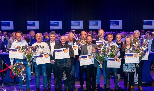 Ed den Besten (3e v l.) en Rabobankmedewerker en presentatrice Esther Stumpf tijdens de finaleavond van 2017 tussen blije bestuurders met hun cheques met een mooie bijdrage.