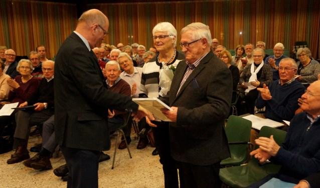Voorzitter Dirk Beerta overhandigt een certificaat aan scheidend lid Mink Mooiman.