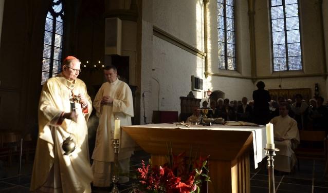 In het volle zonlicht begeeft kardinaal Willem Eijk zich na binnenkomst in de Sint Andreaskerk naar het altaar. Eijk is hoofdcelebrant in de eucharistieviering in verband met de fusie van de parochies Sint Willibrordus en Vier Heilige Evangelisten.(foto: Ab Hendriks)