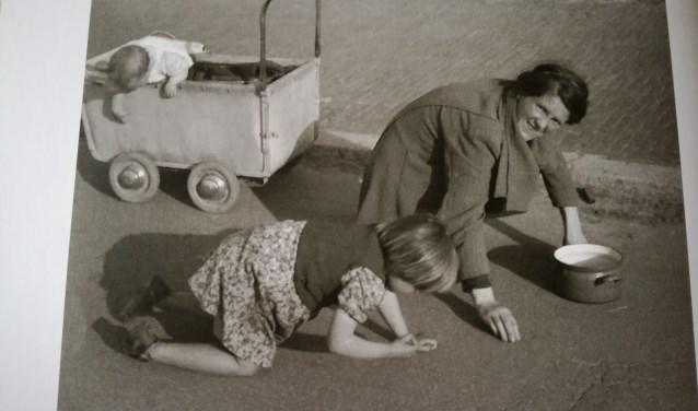 Een foto uit het boek van Trudy van der Wees, moeder met kinderen eten van de straat.