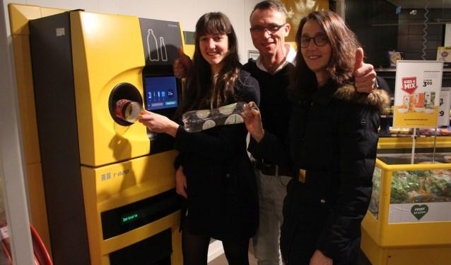 Jacorien (links) en Corina van Walsem samen met Cornelis Mostert van Jumbo Rhenen, bij de flesseninname. (Foto: Henk Jansen)