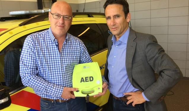 """Leo Roos (links) en directeur van de ambulancedienst Hans Janssen met een levensreddende AED: """"Wij werken er graag aan mee om het gebruik en het bezit van een AED zo laagdrempelig mogelijk te houden."""" (foto: pr)"""