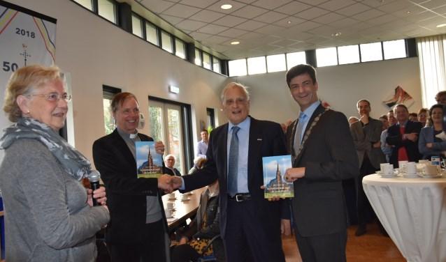 Auteur Henk Groeneveld overhandigt het boek aan Pastoor Winfried Kuipers en aan burgemeester Pieter van de Stadt. Foto: Amel Bali