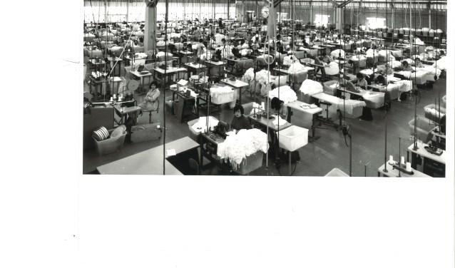 Buffelen in de Hollandia Tricotage aan de Kerkewijk. Een beeld uit de tijd dat Veenendaal nog echt een fabrieksstad was. Op de expositie zijn foto's hiervan te zien. (Foto: Gemeentearchief Veenendaal)