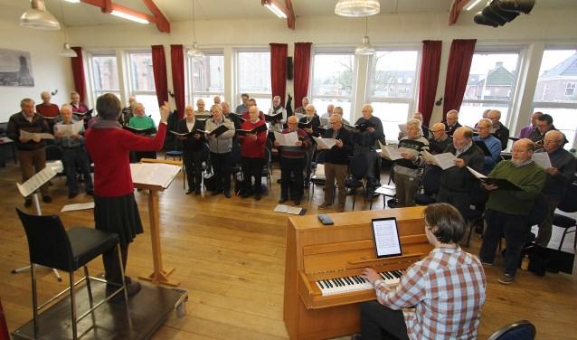Onder leiding van dirigent Monique Verhoeven repeteert het Elster Mannenkoor op een zaterdagmorgen nog eens extra voor het nieuwjaarsconcert. Dat optreden is komende zondag in de Grote Kerk in Elst. (foto: Kirsten den Boef)