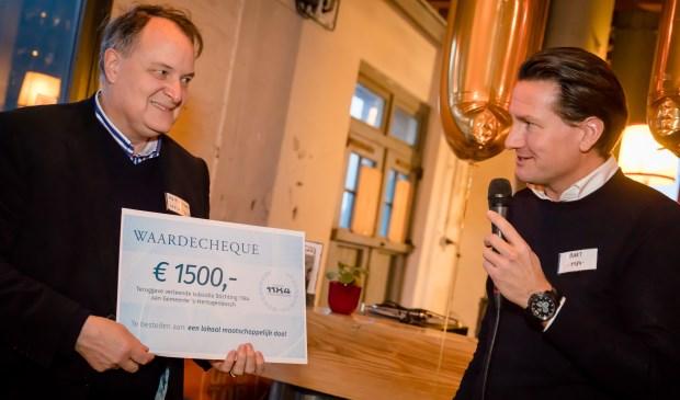 Wethouder Huib van Olden krijgt symbolisch de 1.500 euro subsidie terug van Stichting 1184 uit handen van afzwaaiend voorzitter Bart Huijs.