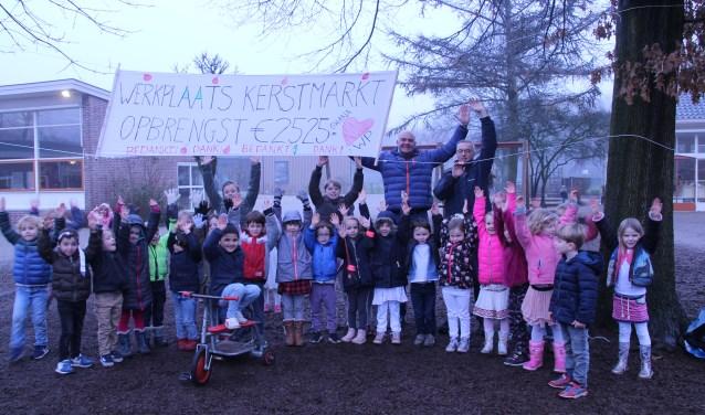 De jaarlijkse kerstmarkt door kinderen van de Werkplaats leverde ook een mooie donatie op.  De kinderen poseren samen met teamleider Hans Kloosterman en John van Deemter.