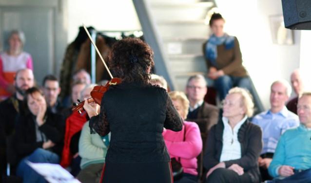 De zaal zit vol, een enkele luisteraar zit op de trap of leunt tegen de wand. Esther Apituley speelt altviool tijdens het 7e concert in de serie concerten Zoden aan de Dijk in de IJsselstroom. (foto: Feikje Breimer)