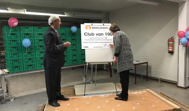 Burgemeester Wobine Buijs zet haar handtekening als eerste lid van de Club van 100 van Voedselbank Oss en Omgeving. Dit deed zij op uitnodiging van haar voorganger Herman Klitsie, links op de foto.