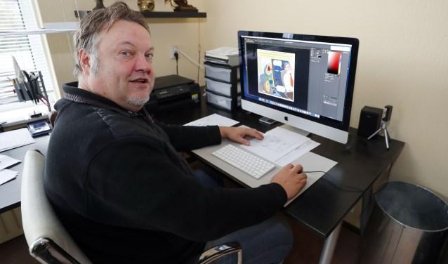 Geert Retera aan zijn werktafel. Meer dan zijn favoriete pen heeft hij niet nodig. Foto: Bert Jansen