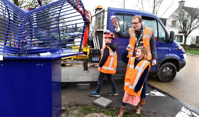 Abe (10) en zusje Valerie (7) mikken samen met burgemeester Mark Boumans afval in de nieuwe blikvanger.