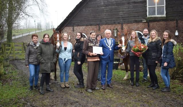 Henk Oudshoorn, burgemeester Dirk van der Borg staan in het midden van de groep verzorgers.