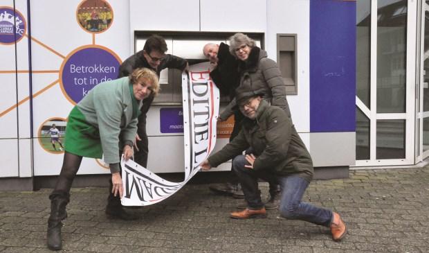Een 'banner' van de talkshow Editie Leerdam rolt uit de pinautomaat van de Rabobank. Foto: Martin van 't Hart