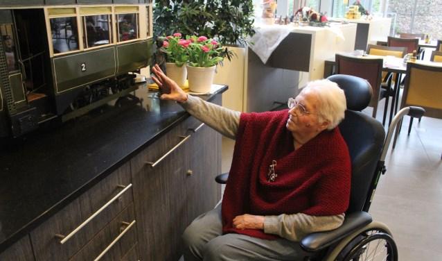 Aaltje van Laar-Jansen (91) wijst naar een van de compartimenten van de miniatuur-tram waarin ze vaak de rit naar Wageningen maakte. De tram staat in een huiskamer-setting in woonzorgcentrum De Tollekamp aan de Nieuwe Veenendaalseweg.  (Foto: Henk Jansen)
