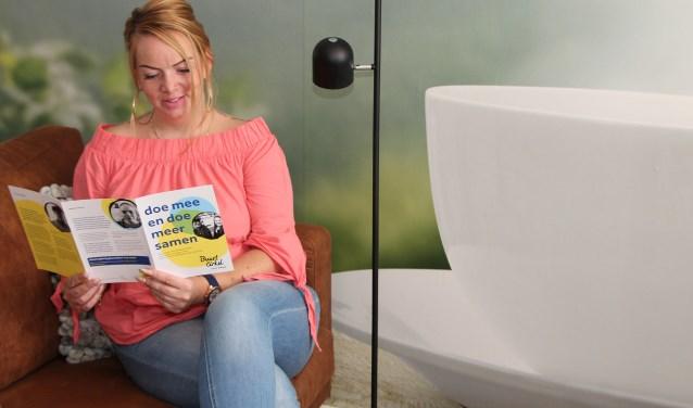 Tineke Mensing leest in de thuiskamer van Pameijer over de Buurtcirkels.