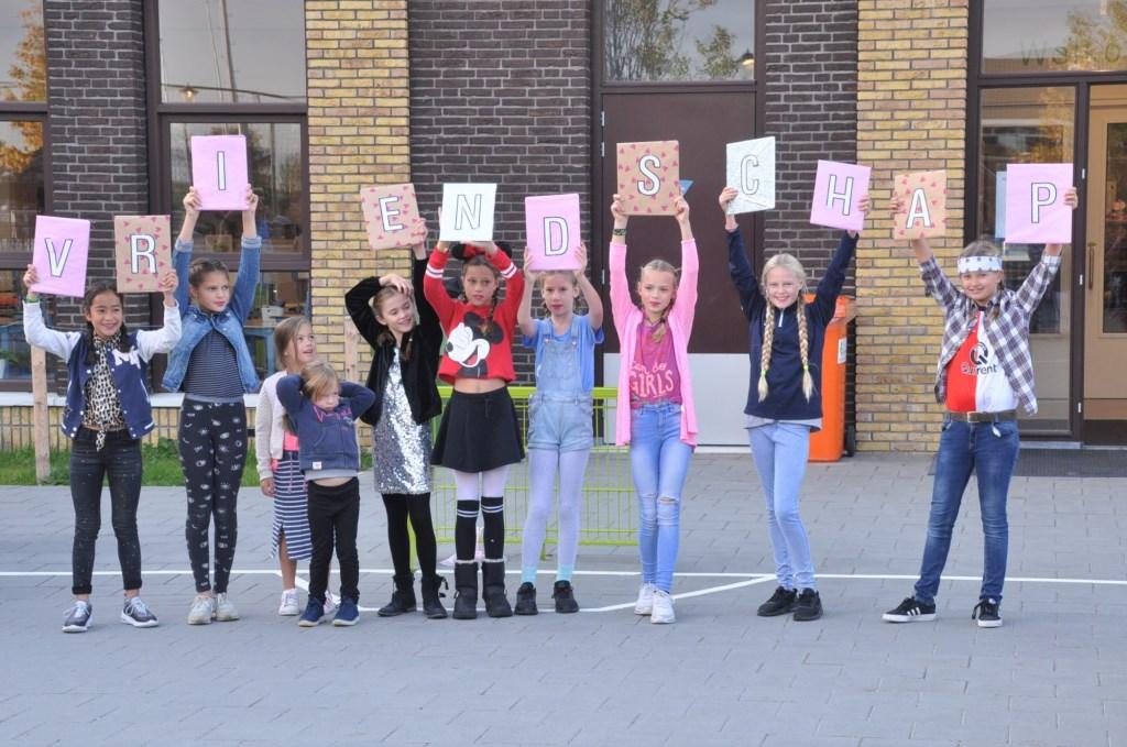 Kinderen vormen het woord 'vriendschap', thema van deze Kinderboekenweek Foto: Maurice van de Lisdonk © Persgroep