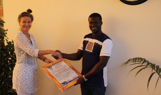 Anane Korsah overhandigde een oorkonde aan Anne-Mieke Bulters als dank voor de (financiële) steun.