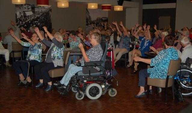 """Gasten en vrijwilligers van de Zonnebloemafdeling Zevenaar-West reageren enthousiast op de """"muziek uit de oude doos"""" van Hans Vesterink"""