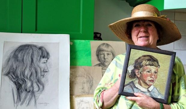 """Truus met de verschillende portretten die haar broer Gerrit Kloens van haar maakte toen ze nog thuis woonden. """"Je werd af en toe gek van dat stil zitten."""" (foto: Elisa Kuster)"""