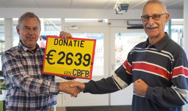 De penningmeester van de CBFB overhandigt nog één keer een cheque aan de voorzitter van de Manege zon-der Drempels: met trots maar ook met een flinke portie weemoed.