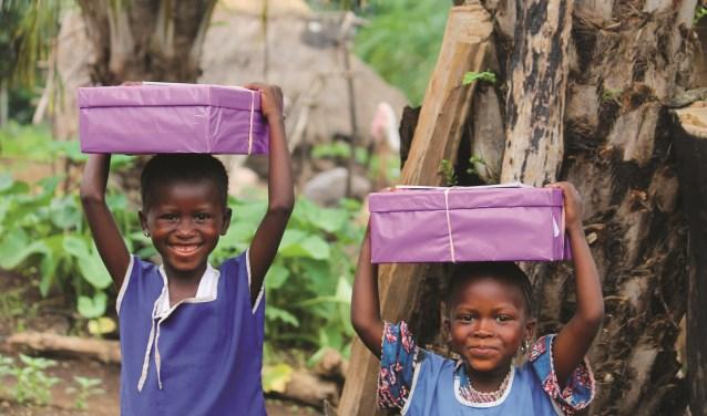 Twee kinderen nemen blij hun gevulde schoenendoos mee naar huis!