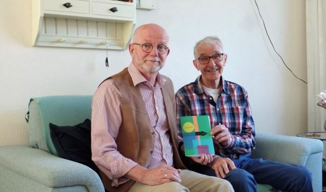 Joop Tessers (rechts) en Marcel Vaandrager laten trots te omslag van zijn dichtbundel zien.
