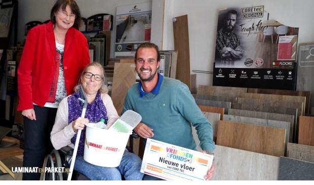Joeke (midden) wordt bij vloerenhandel LaminaatenParket.nl verrast met een cheque van het VriendenFonds van de VriendenLoterij