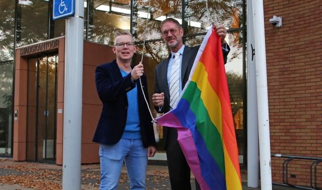 Wethouder Bob Duindam van Oudewater en Remon van Breukelen hijsen de regenboogvlag.