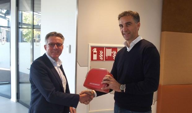 Wethouder Jan Berkhoff overhandigde het koffertje aan de heer Vreekamp.