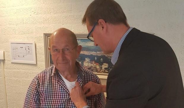 Henk van Falier ontving uit handen van District bestuurslid Ben Visser een oorkonde en verenigingsspeld als blijk van waardering.
