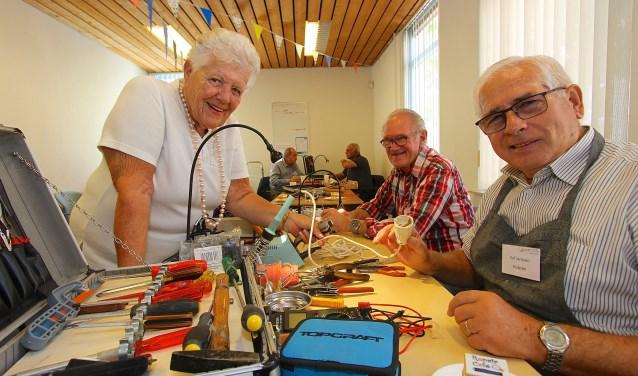 Riek Schuil laat tijdens het Repair Café in Huissen een stekker maken door Eef Janssen (foto: Kirsten den Boef)