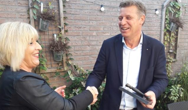 Marco Schuurman ontvangt het  makelaarsstafje uit handen van Hanita Arns.